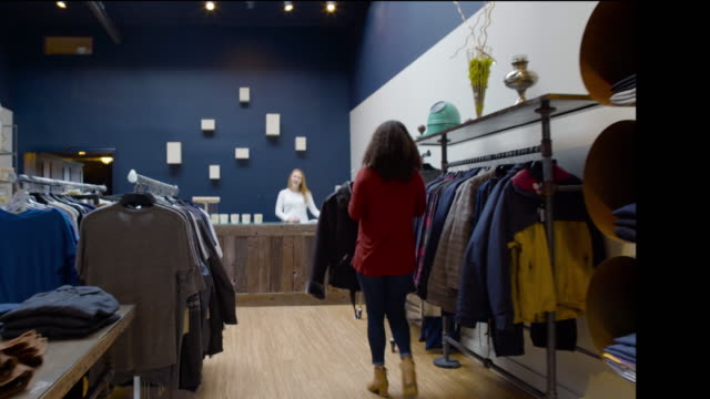 tracking shot of a woman buying a jacket - tracking shot stock videos & royalty-free footage