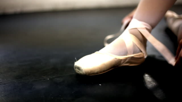 Tracking shot of a woman in ballet shoes.