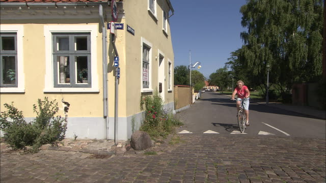 Tracking shot of a woman on a bicycle rounding a corner
