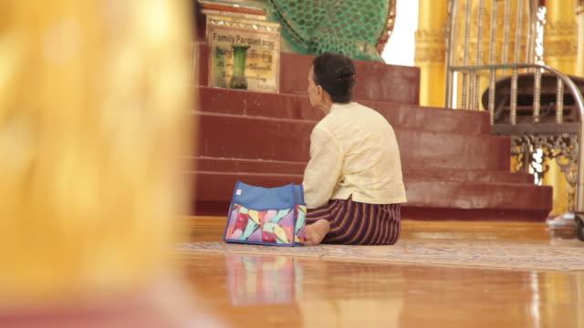 Tracking shot of a woman praying inside the Shwedagon Pagoda.