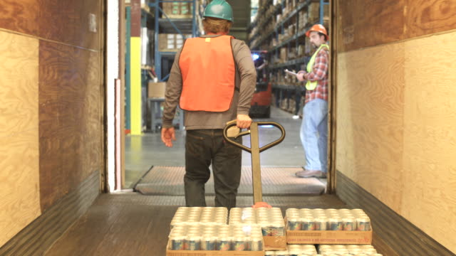 Tracking shot of a worker pulling a pallet truck