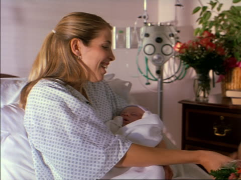 tracking shot of a young caucasian mother with her new baby as her husband and daughhter arrive to visit her in the hospital
