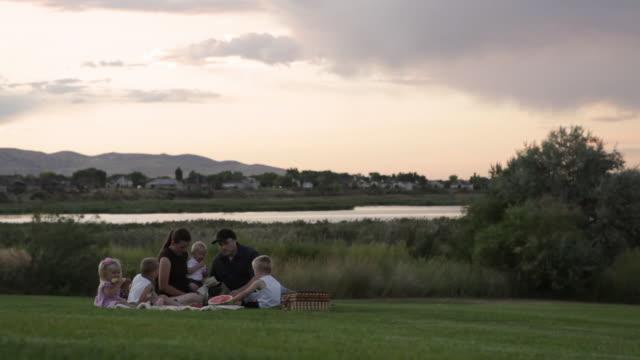 vídeos de stock e filmes b-roll de a tracking shot of a young family of six having a picnic by a lake on a cloudy day at sunset. - família com quatro filhos