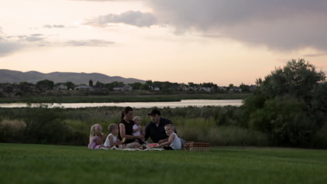 vidéos et rushes de a tracking shot of a young family of six having a small picnic by a lake on a cloudy day at sunset. - pique nique
