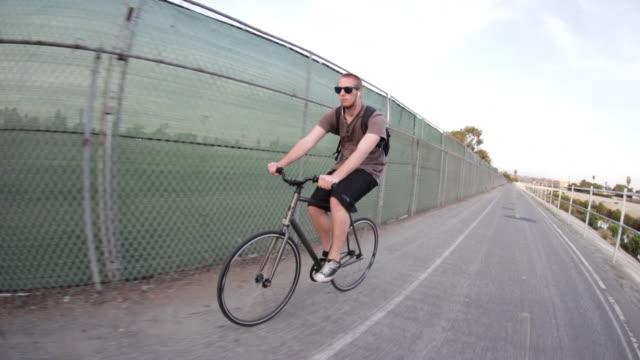 vidéos et rushes de tracking shot of a young man riding his bicycle on a bike path by a creek. - seulement des jeunes hommes