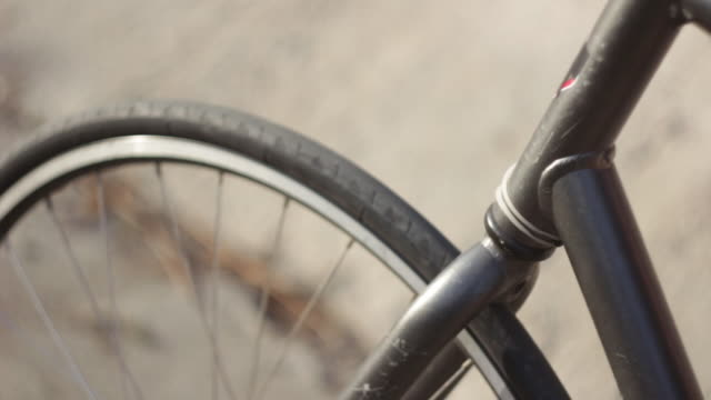 vídeos de stock, filmes e b-roll de tracking shot of a young man riding his bicycle on a bike path by a creek. - goodsportvideo