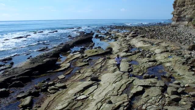vídeos de stock, filmes e b-roll de tracking shot of a young man running on a rocky ocean beach shoreline. - goodsportvideo