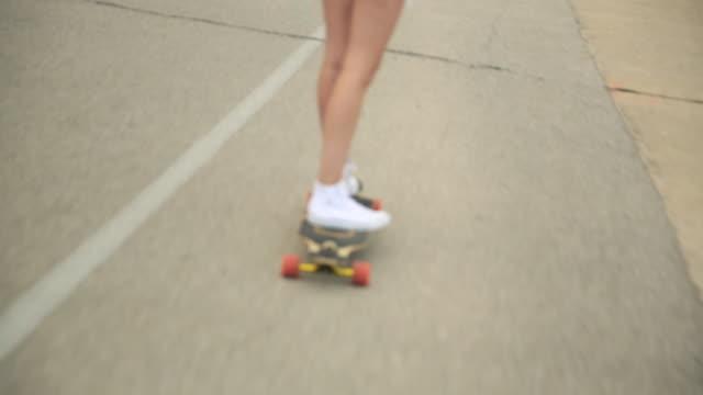 Tracking shot of a young woman going longboard skateboarding.