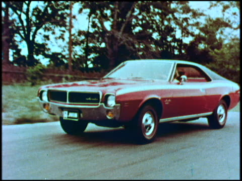 vídeos de stock e filmes b-roll de ws tracking shot of amc javelin on winding road / ms driver side profile woman driving / ws another tracking shot of car on winding road / dissolve... - fotografia de três quartos