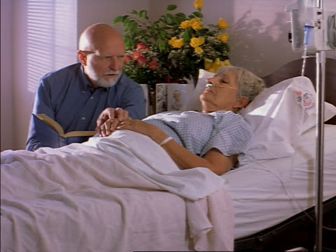 tracking shot of an elderly caucasian man as he reads a book to his ill wife as she lays in a hospital bed - examination gown stock videos & royalty-free footage