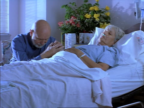 tracking shot of an elderly caucasian man as he sits beside his sick wife in a hospital bed - examination gown stock videos and b-roll footage