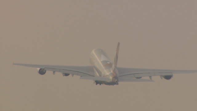 tracking shot of an etihad plane ascending into the grey sky shortly after take off at heathrow airport, london - passagier stock-videos und b-roll-filmmaterial