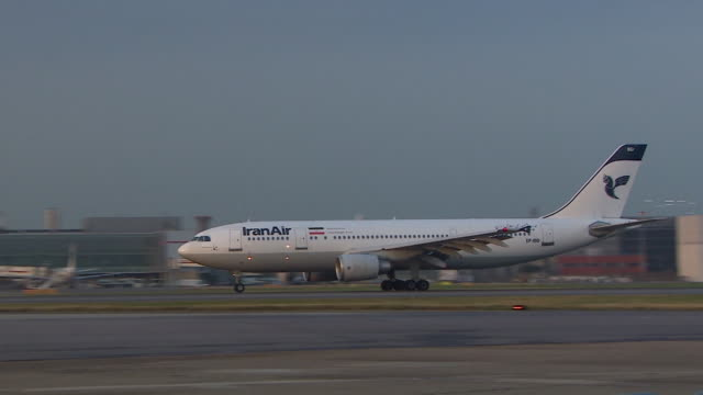 tracking shot of an iran air airbus a300b4 aeroplane taking off from a runway at heathrow airport london - water sports equipment stock videos and b-roll footage