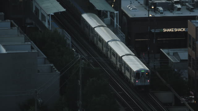 tracking shot of an l train arriving at the morgan station - シカゴ高架鉄道・l点の映像素材/bロール