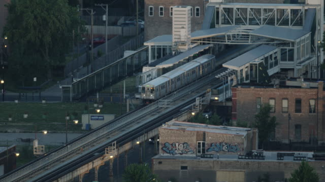 tracking shot of an l train leaving kedzie station on the green line - シカゴ高架鉄道・l点の映像素材/bロール