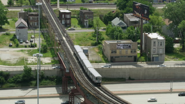 tracking shot of an l train moving on an elevated track - chicago illinois stock-videos und b-roll-filmmaterial