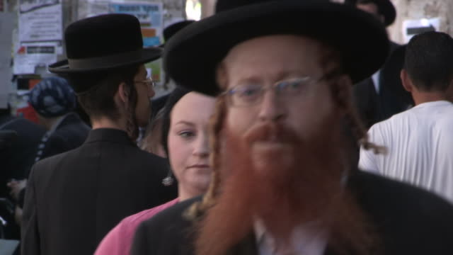 tracking shot of an orthodox jewish man holding a baby on a crowded sidewalk. no audio - gerusalemme est video stock e b–roll
