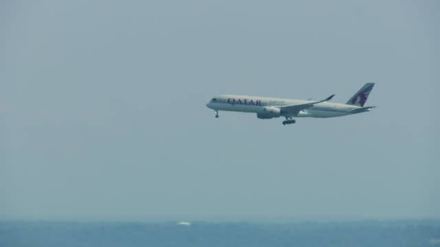 tracking shot of an qatar airways airplane descending over boston - new england usa stock videos & royalty-free footage
