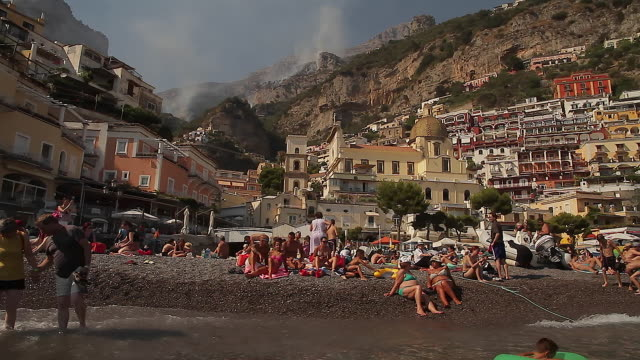 Tracking shot of bathers on Positano beach, Amalfi Coast, Italy