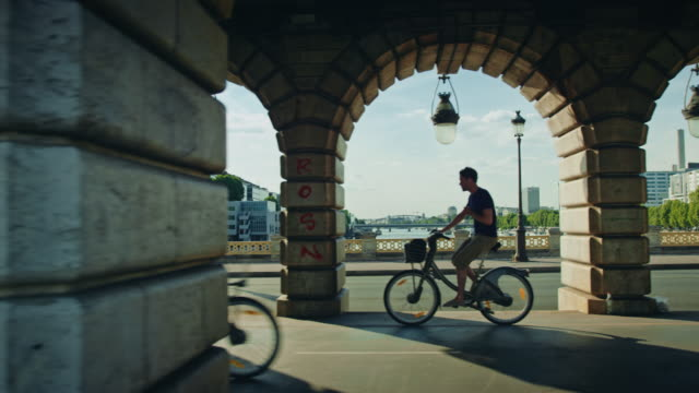 tracking shot of bercy bridge, bicycles passing by - arco architettura video stock e b–roll