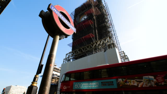 tracking shot of big ben under restoration, underground sign and union flag during lockdown for coronavirus pandemic in london, england, uk, on... - big ben stock videos & royalty-free footage