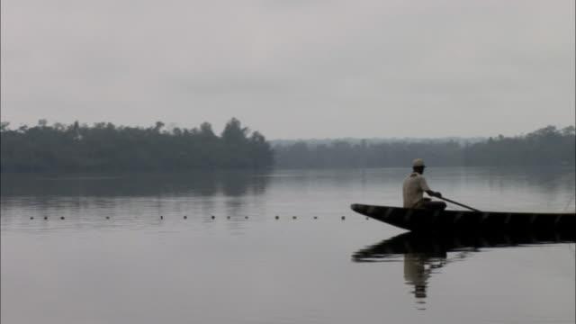 vidéos et rushes de tracking shot of boat carrying fishermen along the wouri river - pêche activité de plein air