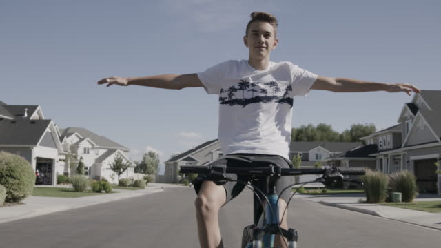 vídeos de stock, filmes e b-roll de tracking shot of boy riding bicycle on suburban street with arms outstretched / lehi, utah, united states - plano americano
