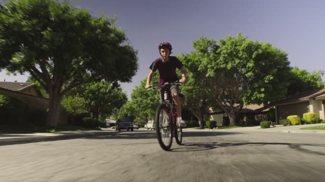 Tracking shot of boy riding bike on residential street in the suburbs