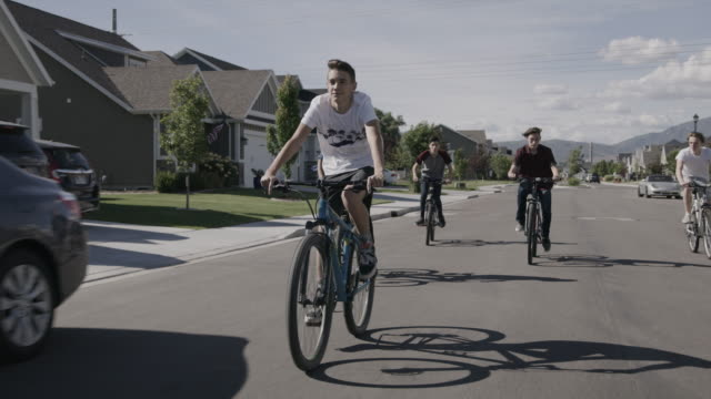 vídeos de stock e filmes b-roll de tracking shot of boys riding bicycles on suburban street / lehi, utah, united states - lehi