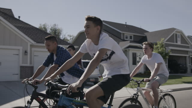 tracking shot of boys riding bicycles on suburban street / lehi, utah, united states - lehi stock videos & royalty-free footage