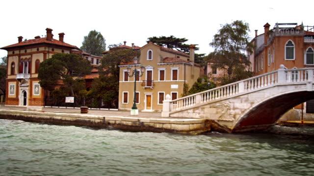 stockvideo's en b-roll-footage met tracking shot of bridge, boat, and buildings along a canal in venice. - venetian causeway bridge