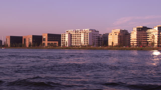 tracking shot of buildings near the eye contemporary movie culture center from the river ij - 北ホラント州点の映像素材/bロール