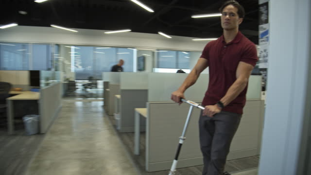tracking shot of businessman riding push scooter in office / pleasant grove, utah, united states - ecke eines objekts stock-videos und b-roll-filmmaterial