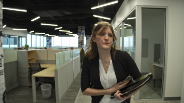 tracking shot of busy businesswoman walking with paperwork and cell phone in office / pleasant grove, utah, united states - hart arbeiten stock-videos und b-roll-filmmaterial
