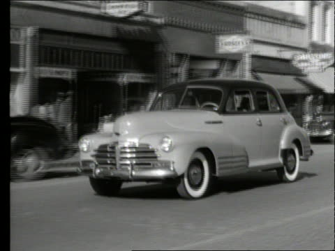 vidéos et rushes de b/w 1948 tracking shot of car driving on city street / chevrolet - chevrolet