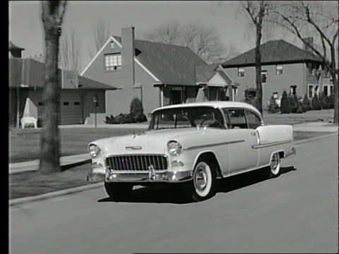 b/w 1955 tracking shot of car driving past suburban houses / chevrolet - two story structure stock videos & royalty-free footage