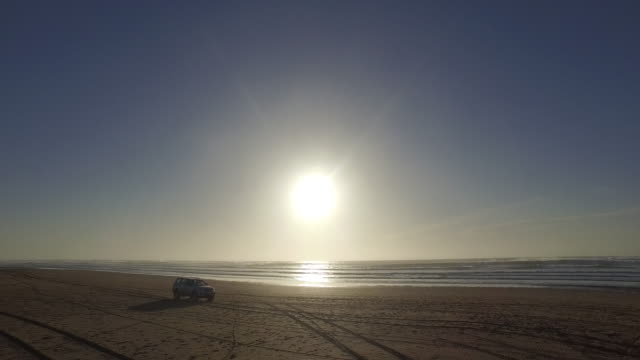 Tracking shot of car moving on beach against blue sky during sunset