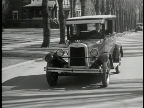 B/W tracking shot of car with man driving on suburban street