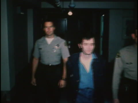 cu tracking shot of charles manson walking down hallway with police officers on both sides of him he has short hair and is somewhat cleanly shaven he... - crime or recreational drug or prison or legal trial stock-videos und b-roll-filmmaterial