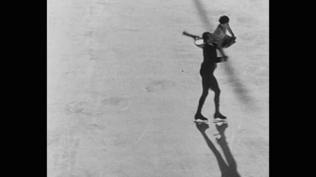 tracking shot of couple dancing while ice skating on ice rink - figure skating stock videos & royalty-free footage
