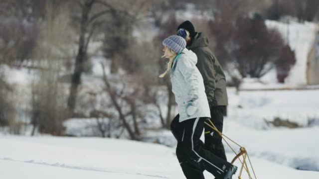 tracking shot of couple pulling toboggan uphill in winter snow / south fork, utah, united states - cappotto invernale video stock e b–roll
