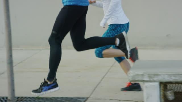 Tracking shot of couple running and jumping on city sidewalk / Salt Lake City, Utah, United States
