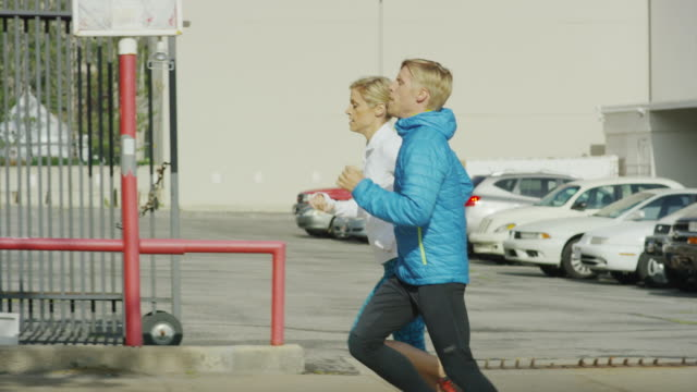 Tracking shot of couple running in neighborhood / Salt Lake City, Utah, United States