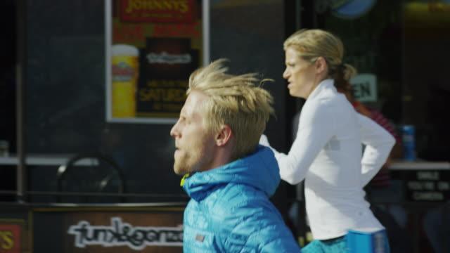 Tracking shot of couple running on city sidewalk / Salt Lake City, Utah, United States