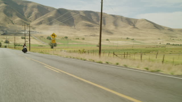 vidéos et rushes de tracking shot of distant woman riding motorcycle approaching then passing / payson, utah, united states - payson