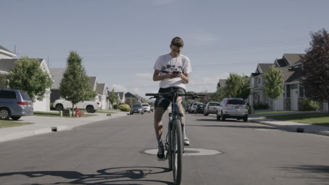tracking shot of distracted boy riding bicycle on suburban street while texting on cell phone / lehi, utah, united states - hosentasche stock-videos und b-roll-filmmaterial