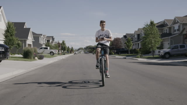 vídeos de stock e filmes b-roll de tracking shot of distracted boy riding bicycle on suburban street while texting on cell phone then turning / lehi, utah, united states - lehi