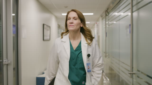 vídeos de stock e filmes b-roll de tracking shot of doctor and nurse passing in corridor and talking / salt lake city, utah, united states - visão frontal