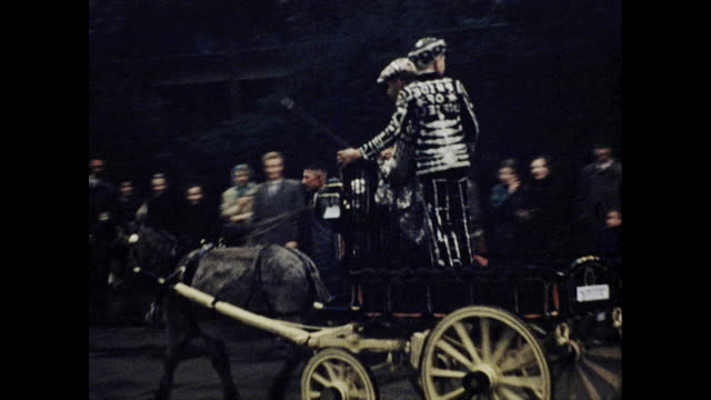 tracking shot of donkey pulled cart with two people on it people standing by the side of the street watching - ウマ科点の映像素材/bロール