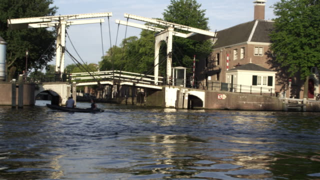 tracking shot of drawbridge and downtown amsterdam in netherlands - drawbridge stock videos and b-roll footage